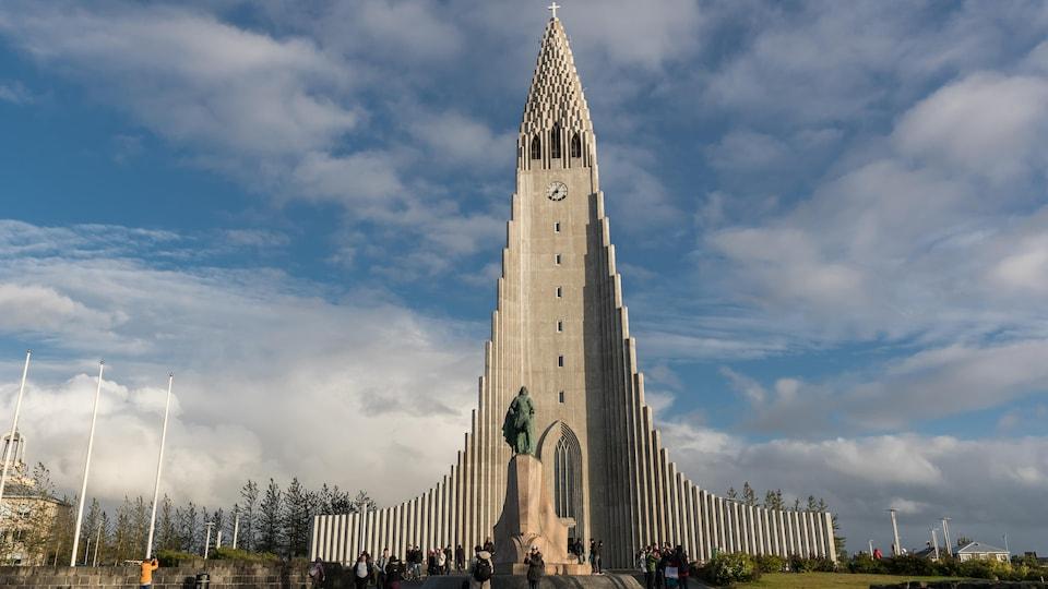Des touristes prennent des photos devant l'église.