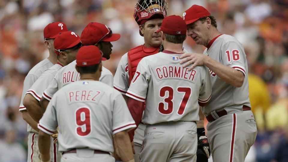 Plusieurs joueurs discutent. Un homme a la main réconfortante sur l'épaule de Cormier.