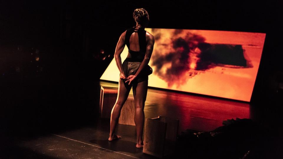 La danseuse est de dos devant un écran orangé.