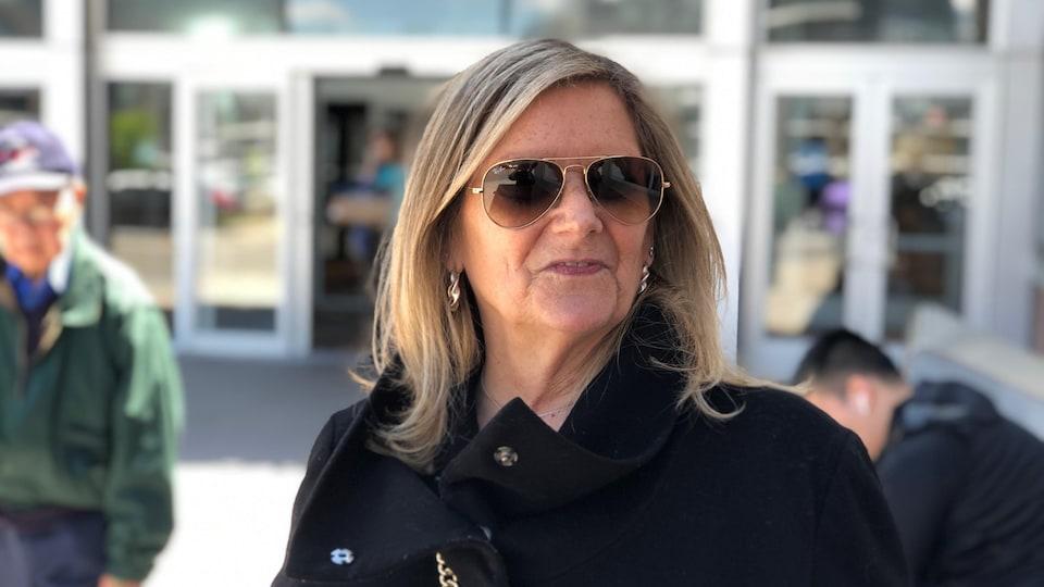 Une femme qui porte des verres fumés répond aux questions d'un journaliste.