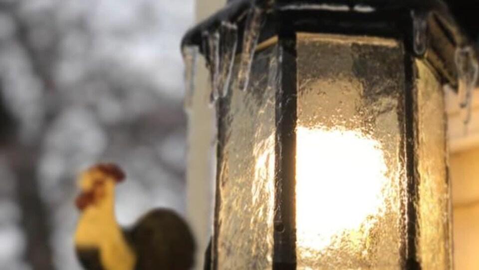 Une lumière extérieure, allumée, recouverte de verglas. Une figurine de coq floue est en arrière-plan.