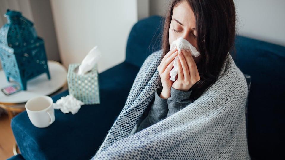 Une femme malade se mouche.