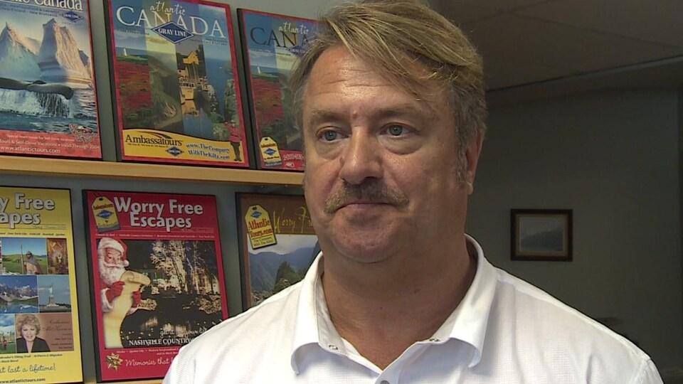 Richard Arnold donne une entrevue. Des magazines de voyage se trouvent derrière lui, dans le décor.
