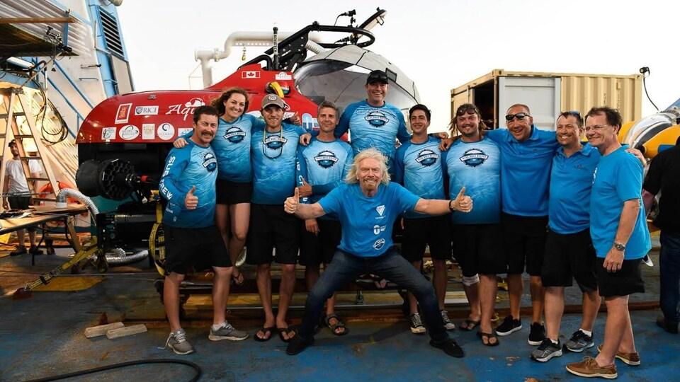 Richard Branson se tient au milieu d'un groupe qui prend la pose en souriant et il brandit ses pouces en avant.