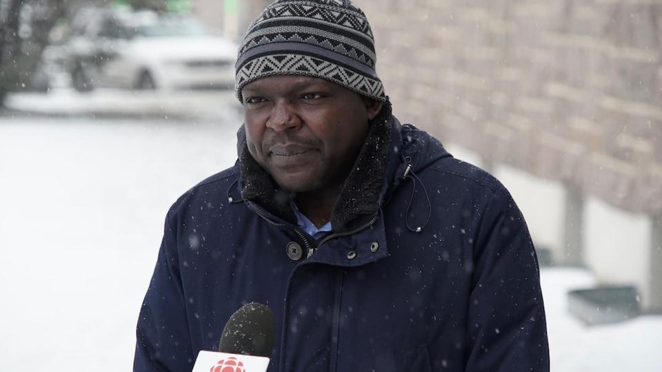 Richard Fachehoun accorde une entrevue à Radio-Canada sous la neige.