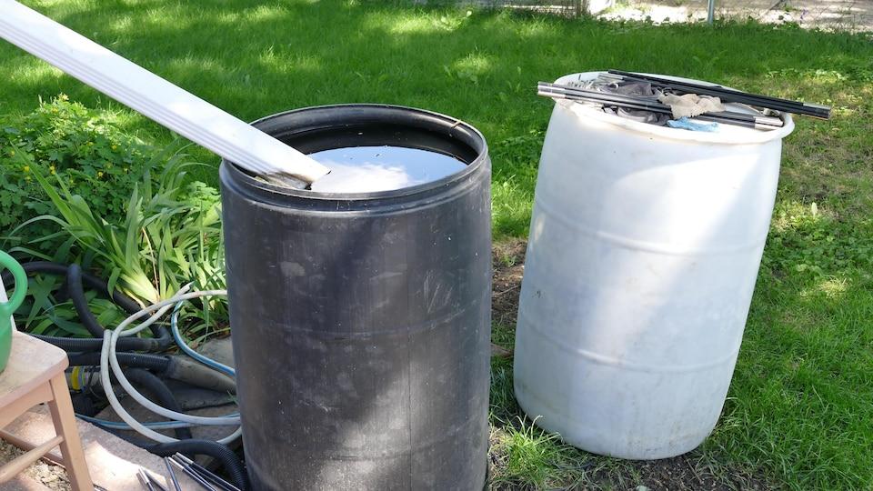 Deux barils, l'un blanc et l'autre noir, récoltent l'eau de la pluie.