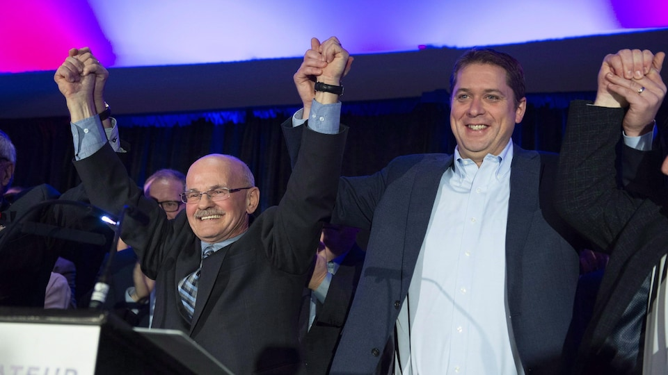 Richard Lehoux et Andrew Scheer, sourient en se tenant la main, les bras dans les airs.
