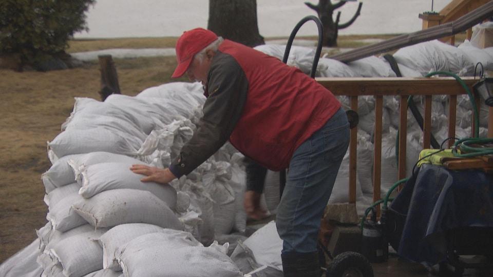 Un homme empile des sacs de sable à l'extérieur de sa résidence.