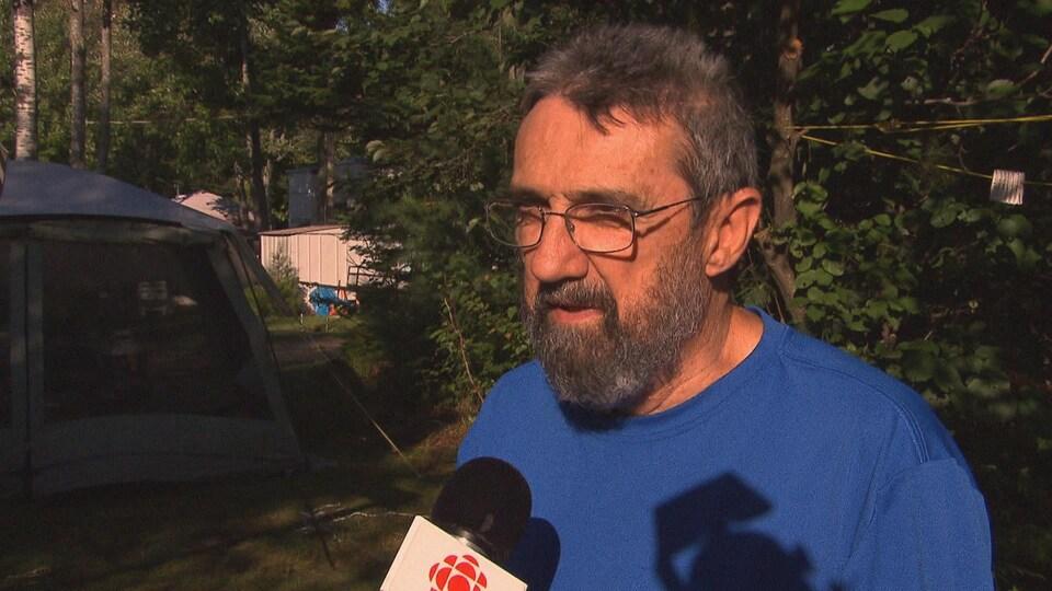 Homme avec le micro de Radio-Canada devant le bois.