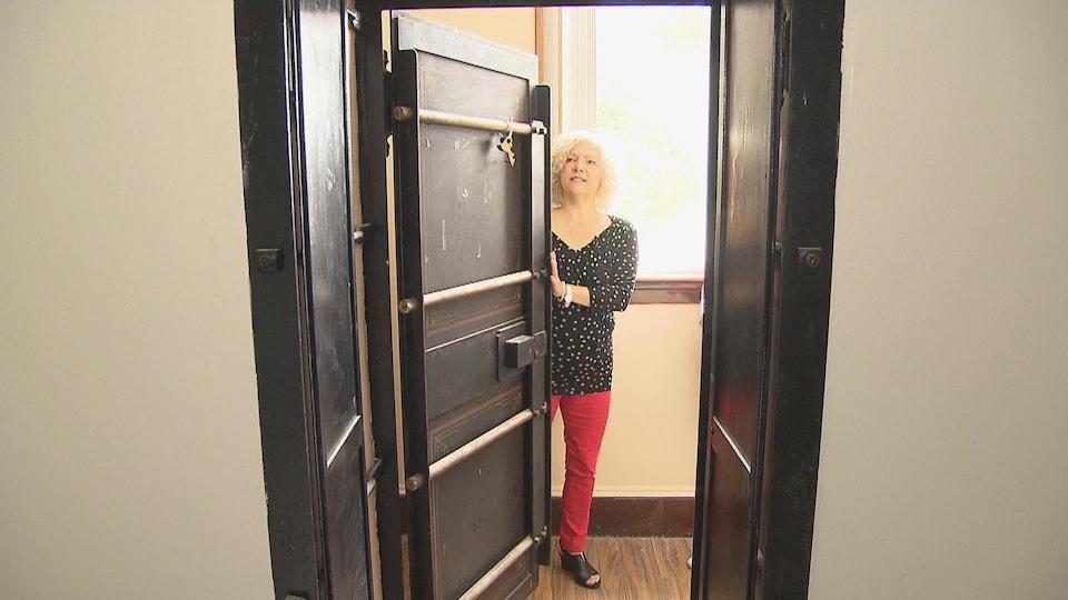 Une femme tient une porte dans un ancien Palais de justice.