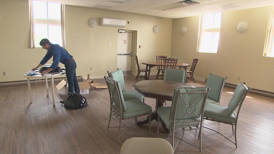 Un homme dépose son matériel sur une table.