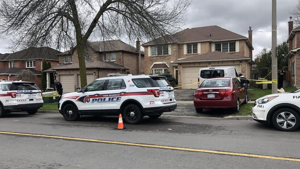 Une voiture de police devant une maison dans un quartier résidentiel.