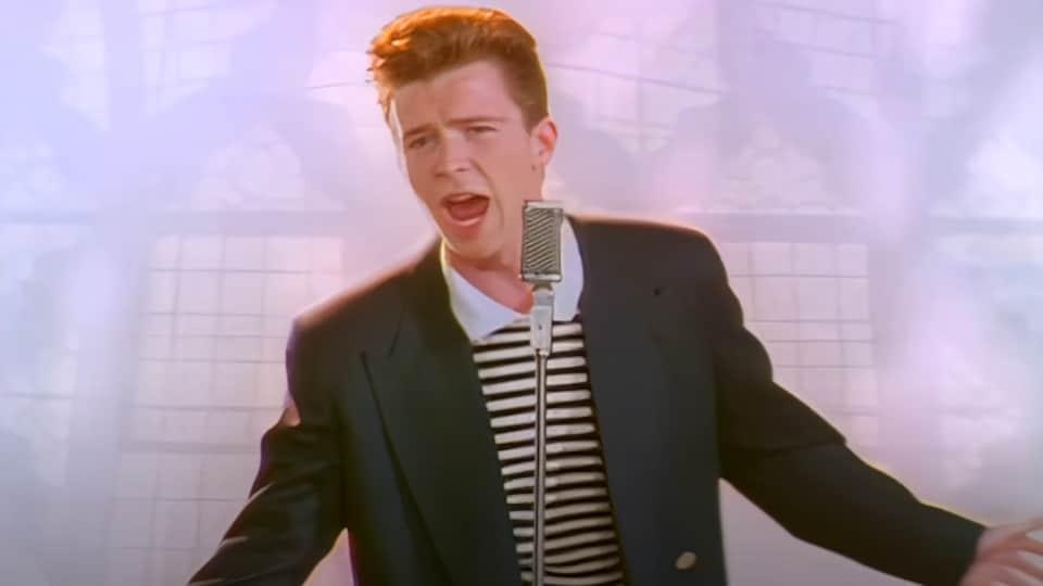 Capture d'écran montrant le jeune chanteur Rick Astley en train de chanter devant un micro, les bras ouverts.