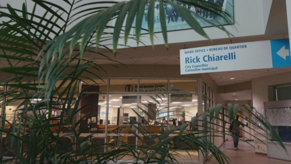 Des plantes se trouvent dans l'édifice, devant une affiche avec le nom du conseiller.