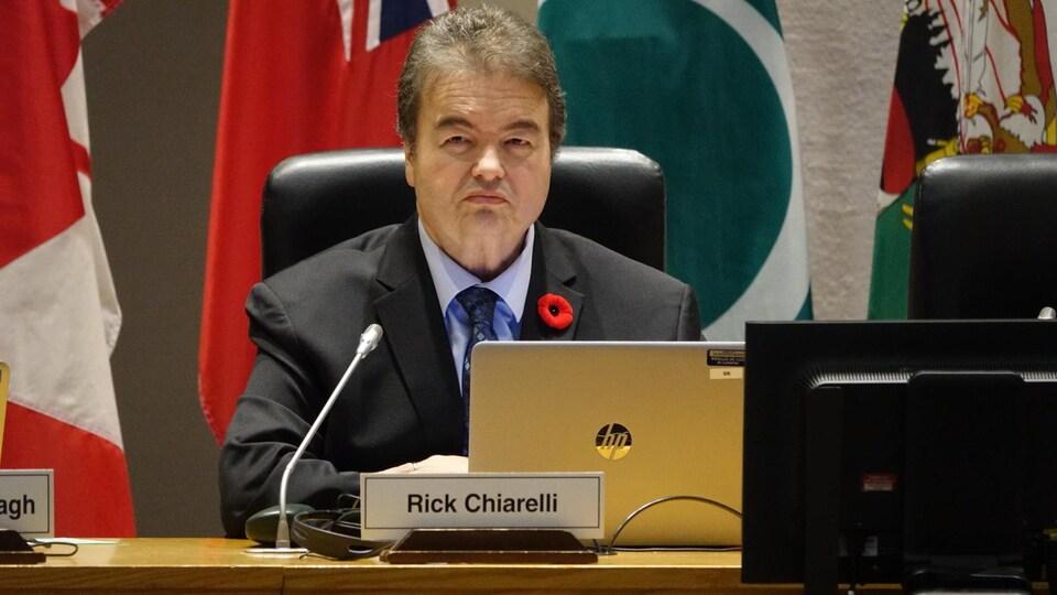Rick Chiarelli assis devant un ordinateur portable et un microphone.