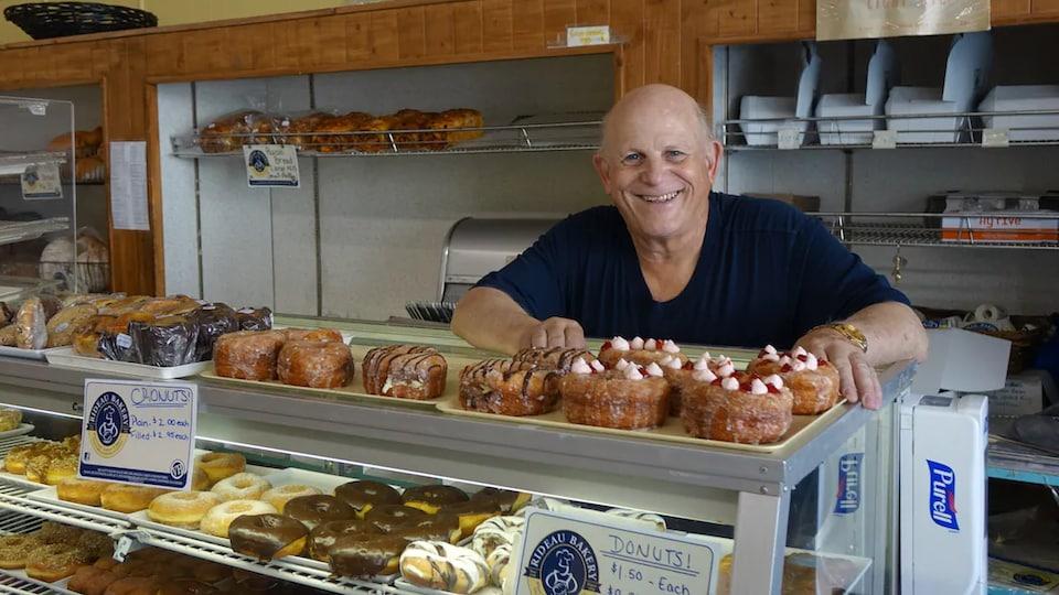 M. Kardish sourit derrière son comptoir de pâtisseries.