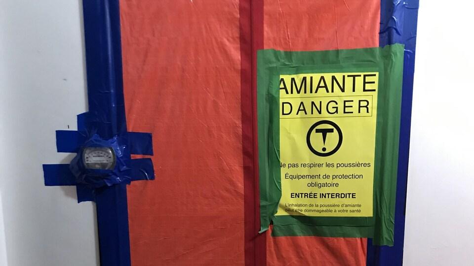 Le mot AMIANTE sur les portes de plusieurs logements vacants.