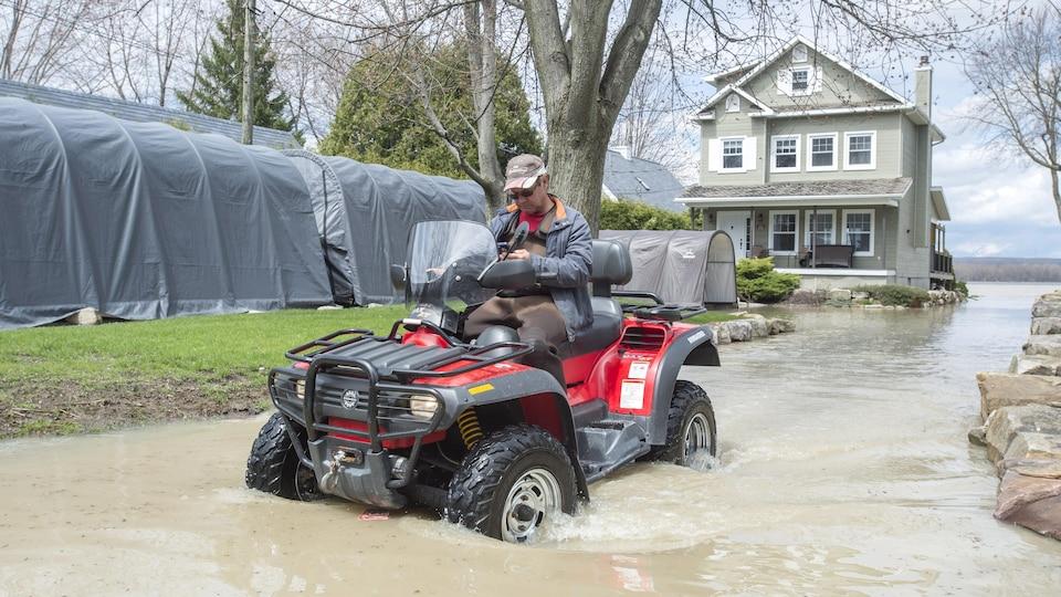 Un homme quitte sa maison inondée à Rigaud, au Québec.
