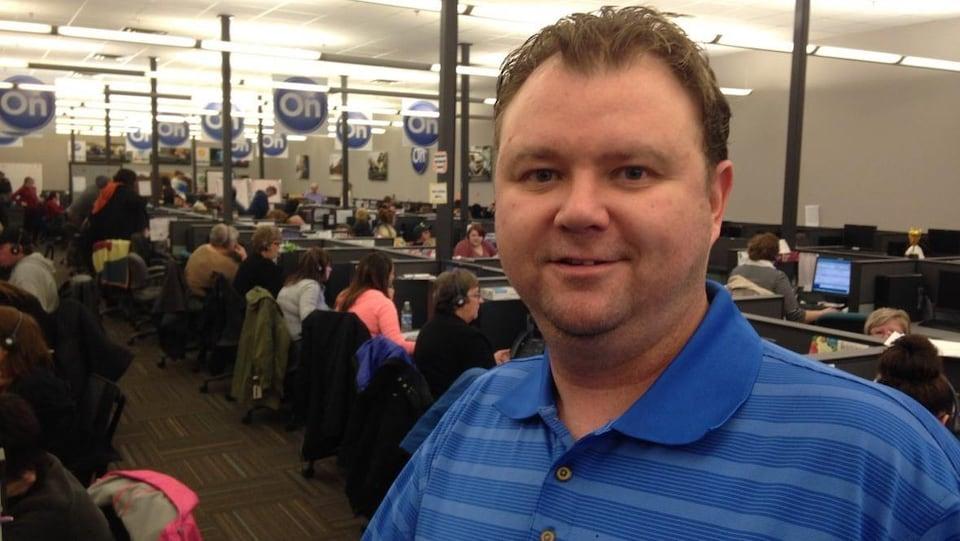 Todd Riley debout devant devant des dizaines d'employés qui travaillent à leur poste