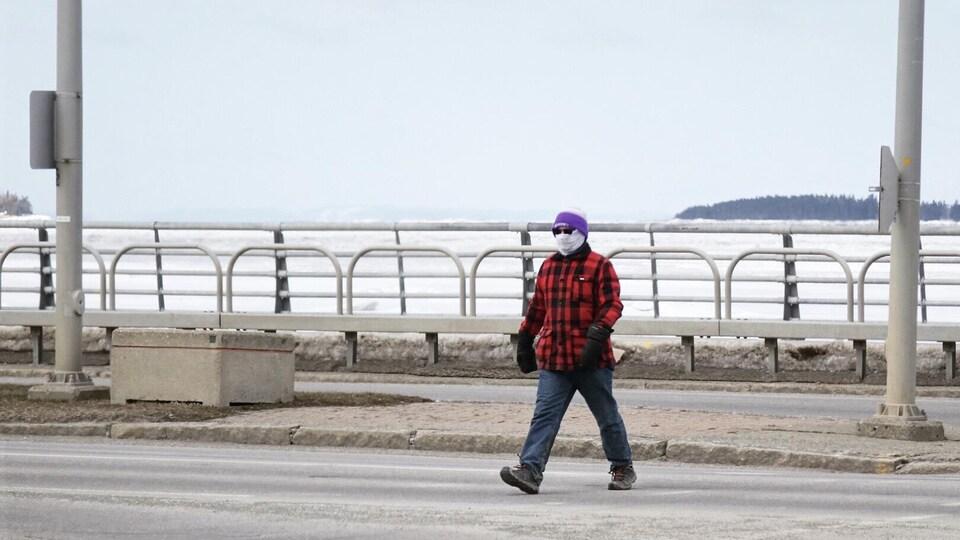 Un homme traverse un boulevard à Rimouski.