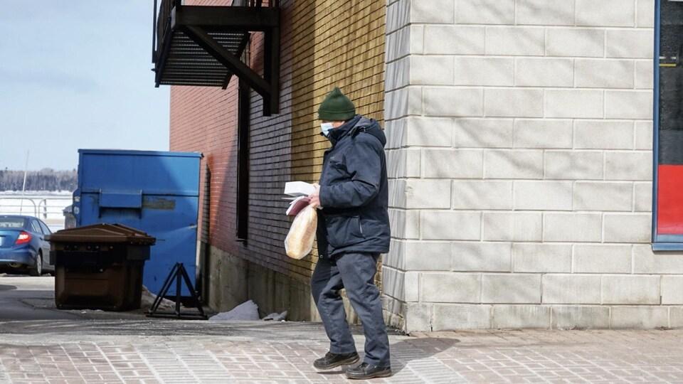 Une personne porte un masque et marche sur le trottoir.