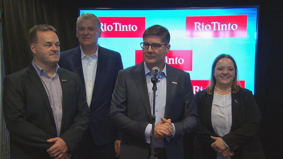 Quatre dirigeants de Rio Tinto répondent aux questions des journalistes devant un micro.