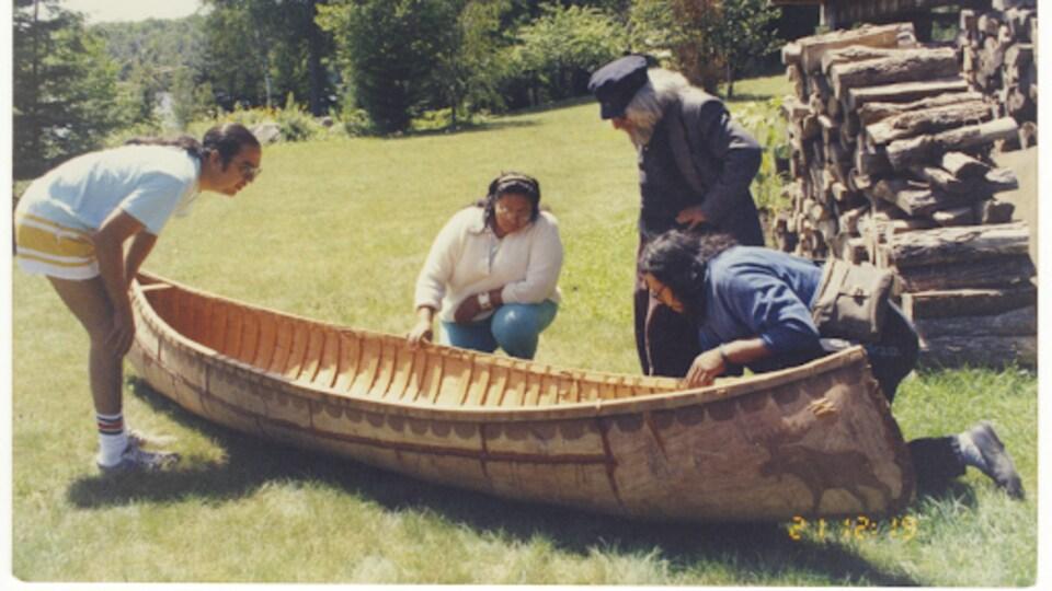 Quatre personnes autour d'un canot.