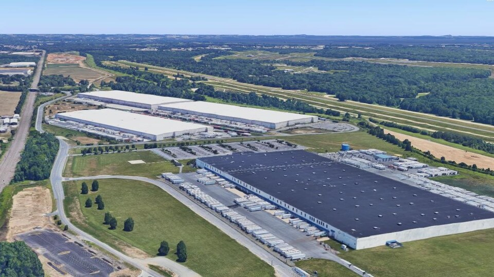Un bâtiment industriel avec quelques camions.