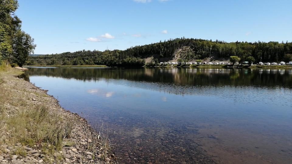 On voit de petites pierres à travers l'eau claire de la rivière. À l'arrière-plan, on voit des véhicules récréatifs stationnés.