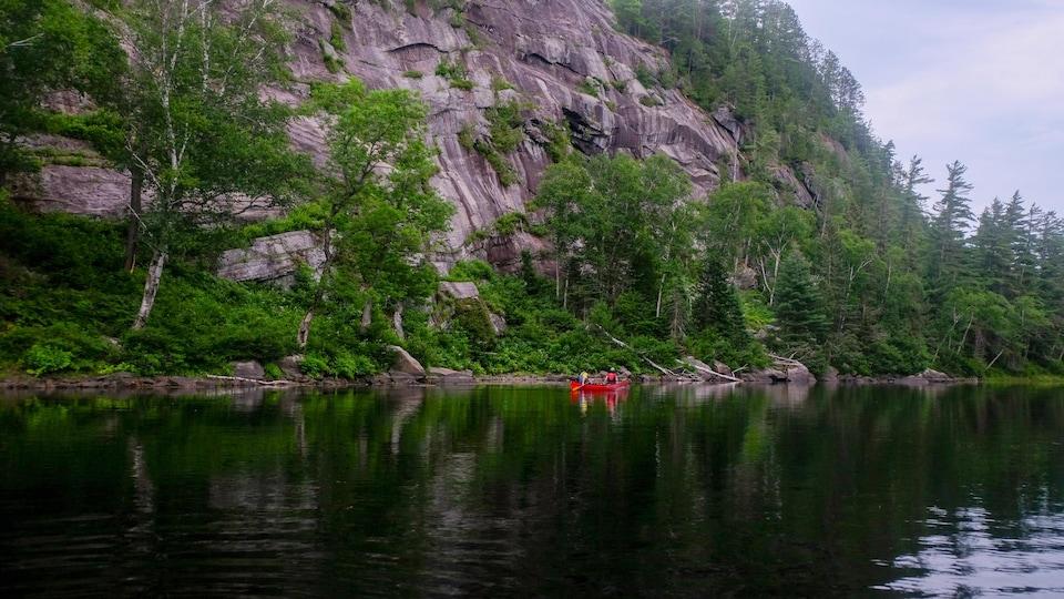 Un canot sur une rivière à côté d'une haute falaise rocheuse.