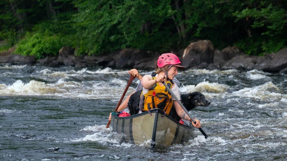 Deux personnes eu un chien dans un canot sur un rapide.