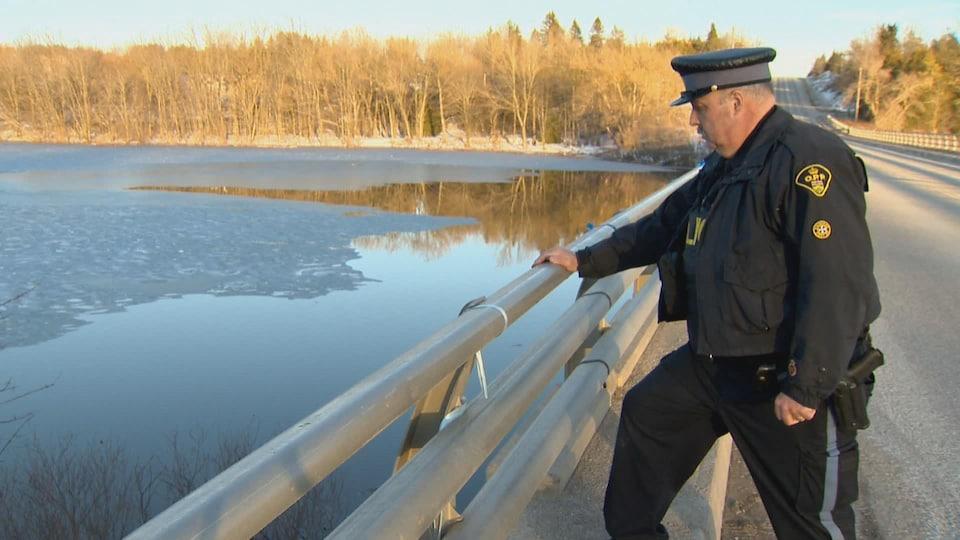 Un agent de la Police provinciale de l'Ontario observe la rivière Grand, près de l'endroit où le corps d'un enfant a été retrouvé.