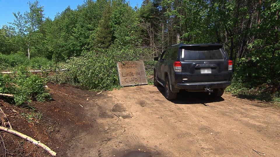 Un véhicule est stationné devant un amas d'arbres qui obstrue le chemin de terre. Une pancarte en bois indique : «accès fermé, limite du club».
