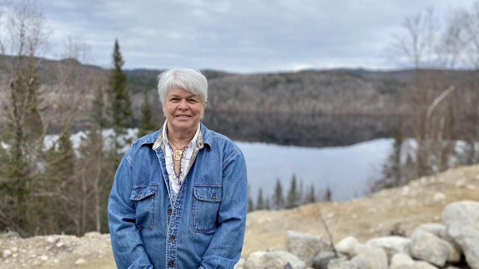 Une femme sourit devant un lac au printemps.