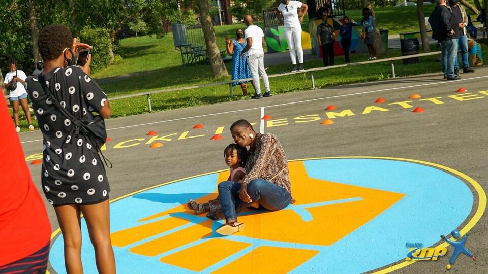 Une femme assise tient un jeune garçon entre ses jambes au milieu d'un terrain de basket, alors qu'une autre femme les prend en photo.