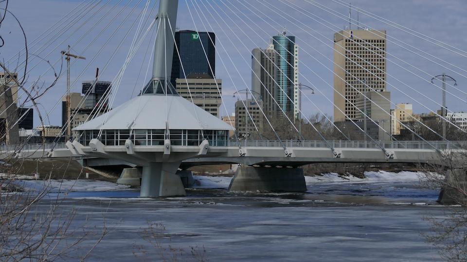 Une rivière, un pont et le centre-ville de Winnipeg à l'arrière-plan.