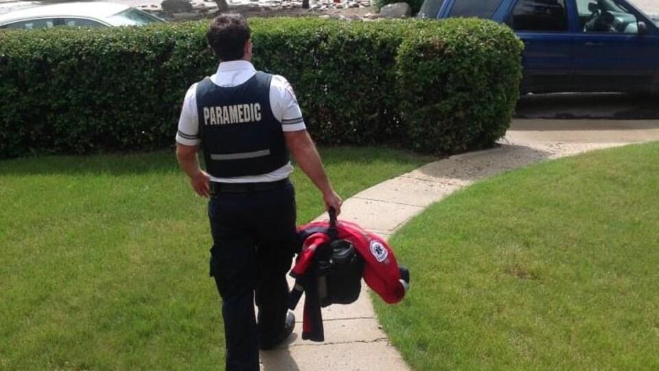 L'homme quitte sa résidence vêtu de son uniforme et de son sac de travail à la main.