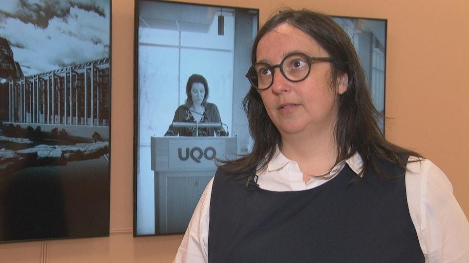 Une femme avec de longs cheveux bruns porte des lunettes rondes foncées. Elle est debout devant un écran où on voit une reconstitution du point de presse fait par les dirigeants du MBAC lors du dévoilement de la robe de chair de Jana Sterbak.