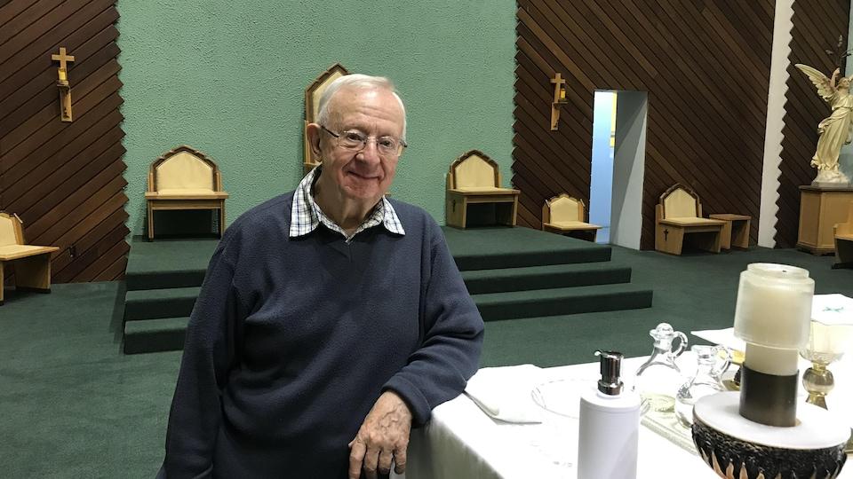 L'homme est debout dans une église de Rouyn-Noranda.
