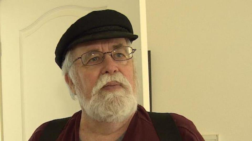 Un homme barbu se tient debout dans une chambre.
