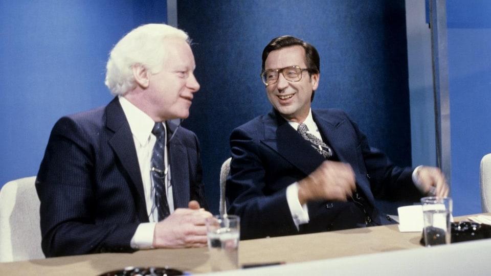 Dans un studio de télévision, Pierre Bourgault et Robert Bourassa discutent, assis à la même table.