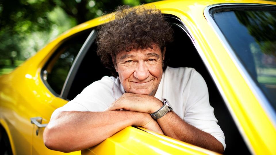 Robert Charlebois sourit dans une voiture jaune.