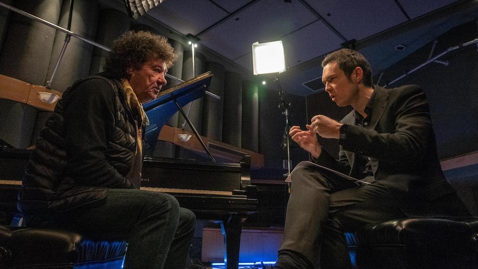 Deux hommes, assis face à face, discutent autour d'un pioano à queue.