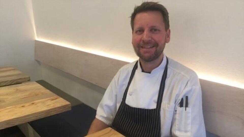 Robert Clarke assit devant une assiette avec deux tacos, dans le restaurant The Arbor.