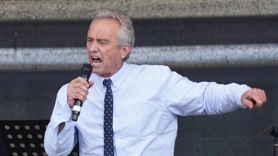 Un homme tient un micro dans les mains, parle avec conviction et pointe vers sa gauche.