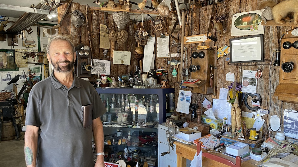 Un homme âgé sourit à la caméra devant des objets antiques liés à la drave.