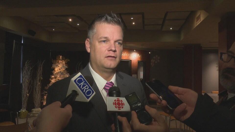 Robert Gauvin, vice premier ministre et ministre responsable de la Francophonie au Nouveau-Brunswick, devant les micros.