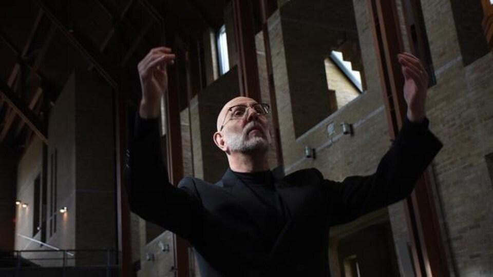 Un homme les bras levés dans un édifice.