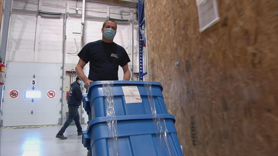 Robert Michaud transporte des bacs de plastique dans un entrepôt.