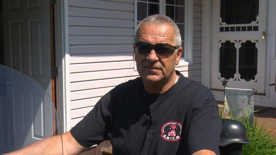 Robert Ouellette répond à des questions à califourchon sur sa moto.